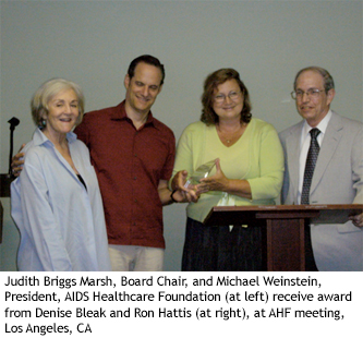 Judith Briggs Marsh, Board Chair, and Michael Weinstein, President, AIDS Healthcare Foundation (at left) receive award from Denise Bleak and Ron Hattis (at right), at AHF meeting, Los Angeles, CA
